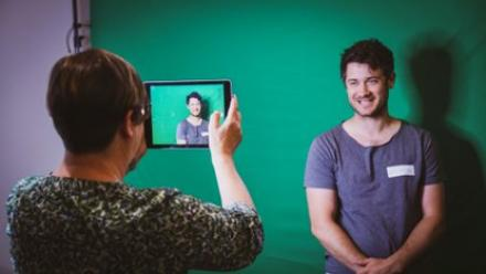 Person filming someone in front of green screen