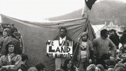 Alan Sharpley with a placard at the Aboriginal Tent Embassy, c.1972. (NLA)