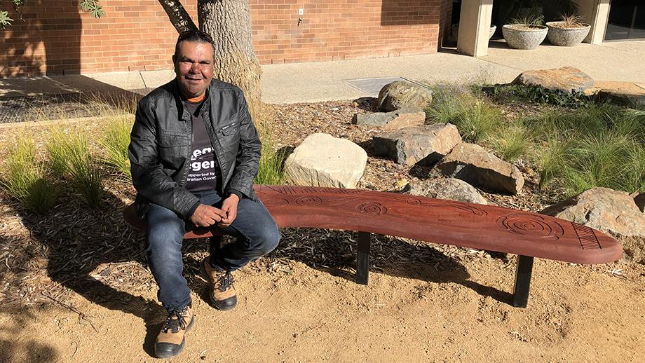 Ngunnawal man Adrian Brown with the carved bench seat he made for the garden