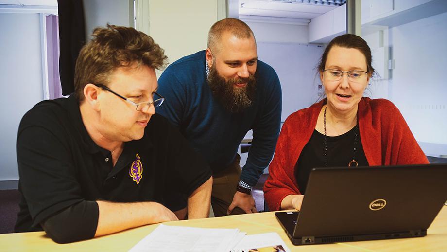 Three Fellows looking at a laptop