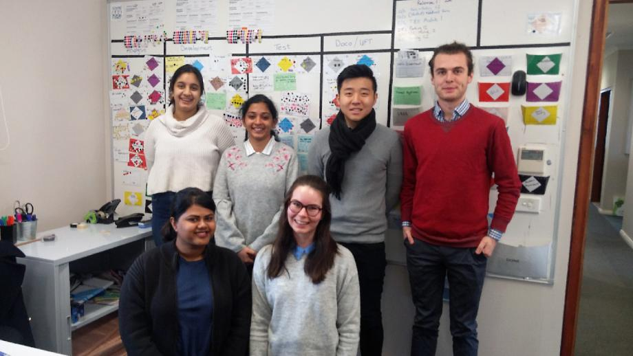 IDTC Interns standing in front of the Agile board
